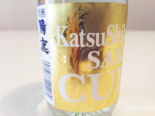 """今回の一杯はカップ酒。金の鹿がラベルの中でしれっと""""シカト""""している『KatsuShika SAKE CUP』を冷蔵庫でキンキンに冷やしておきます。"""