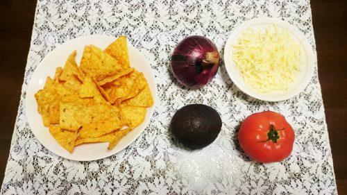 オーストラリア流ナチョスの材料。三角形のスナック、紫たまねぎ、トマト、アボガド、チーズ。
