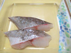 「タラの香草パン粉焼き」の作り方。タラの両面を軽く塩・こしょう(分量外)し、皮を上にして大き目の耐熱皿に載せます。